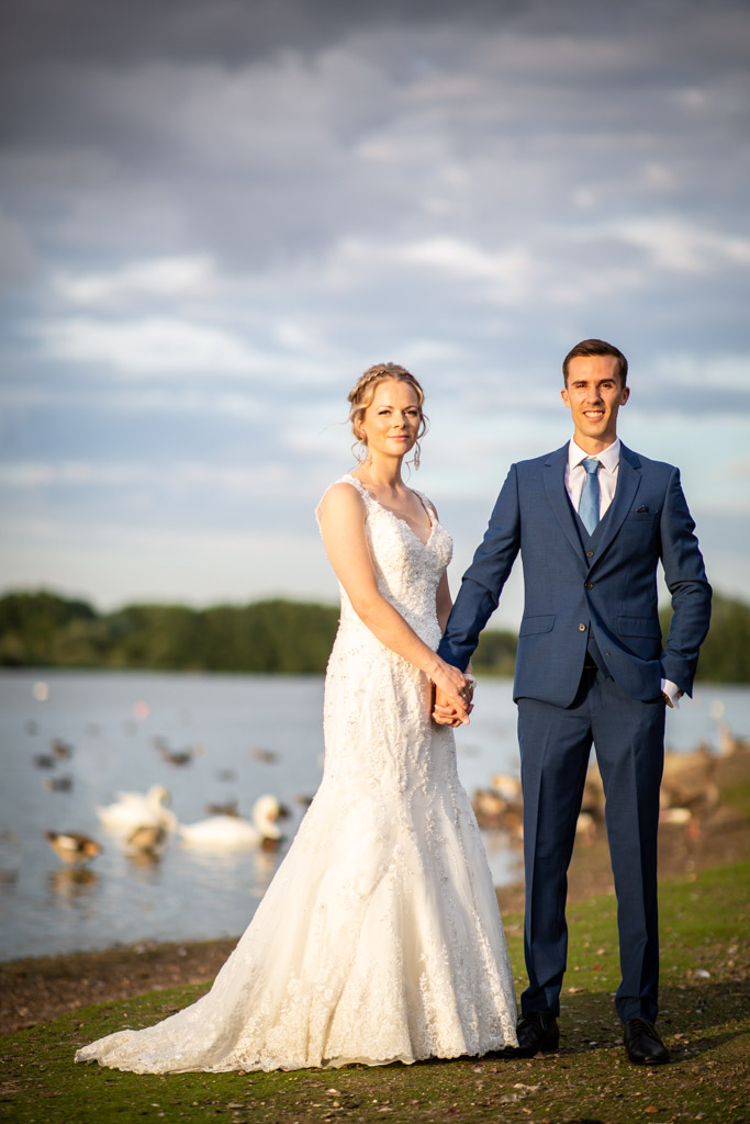 Bride and groom by a lake with swans
