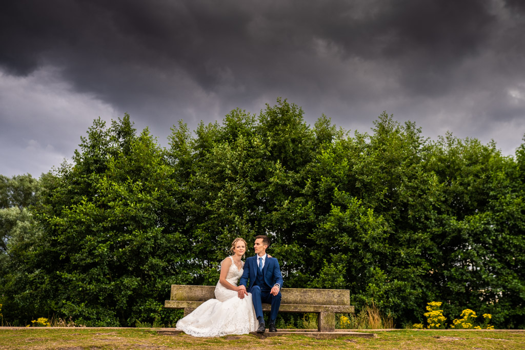 wedding couple sit on a bench under angry black clouds