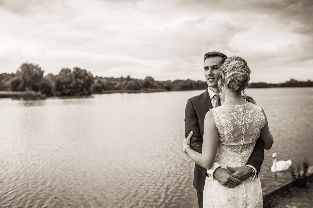wedding couple embrace each other by the waters edge
