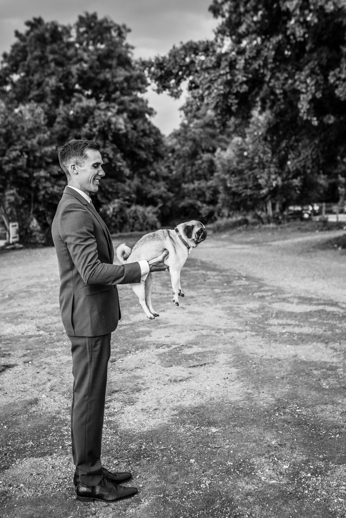 bridegroom holds his pet pug dog