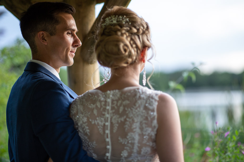 groom looks at bride as she looks out onto a lake