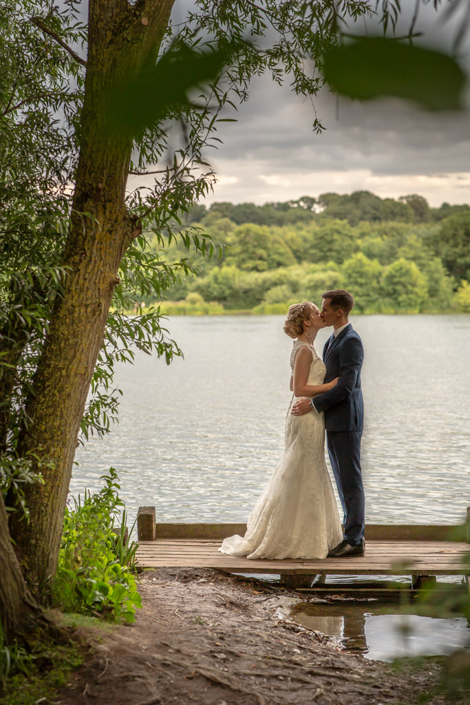 wedding couple kiss by a lake during sunset